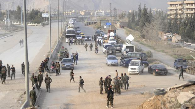Syrian government forces oversee the evacuation by buses of rebel fighters and their families at a checkpoint in eastern Ghouta (SANA via AP)