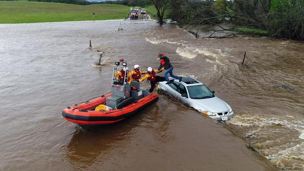 Firefighters from the Folsom, California., Fire Department rescue a man whose car got stuck as a flash flood washed over a road near Folsom (Kelly B Huston/California Governor's Office of Emergency Services via AP)