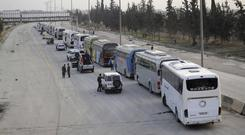 Syrian government forces oversee the evacuation by buses of rebel fighters and their families, at a checkpoint in eastern Ghouta (SANA via AP)