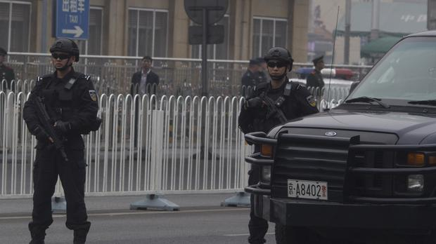 Heavily armed police guard an area outside a train station ahead of the arrival of a convoy in Beijing, China (Ng Han Guan/AP)