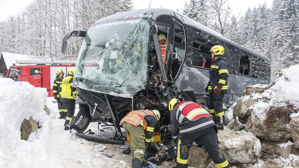 Firefighters work at the wreckage of a bus that crashed in Gosau near Salzburg (Werner Kerschbaumayr /FotoKerschi.at/Kerschbaummayr via AP)