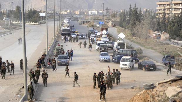 Syrian government forces overseeing the evacuation by buses of rebel fighters and their families, at a checkpoint in eastern Ghouta (SANA via AP)