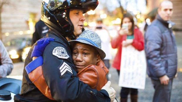 Portland police Sergeant Bret Barnum (left) and Devonte Hart, 12, hug at a rally in 2014 (Johnny Huu Nguyen/AP/PA)