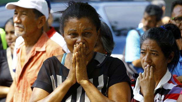 Relatives wait to hear news about the fate of detained prisoners at a police station where a riot broke out, in Valencia, Venezuela (Juan Carlos Hernandez/AP)