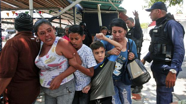 Police officers disperse the relatives of prisoners who were waiting to hear news about their family members imprisoned at a police station when a riot broke out, in Valencia, Venezuela (Juan Carlos Hernandez/AP)