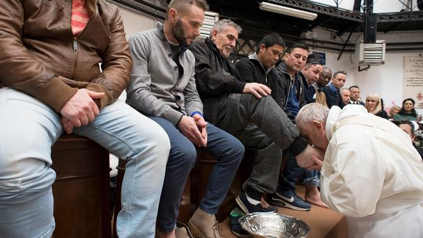 Pope Francis washes the feet of inmates during his visit to the Regina Coeli detention centre in Rome (Vatican Media via AP)