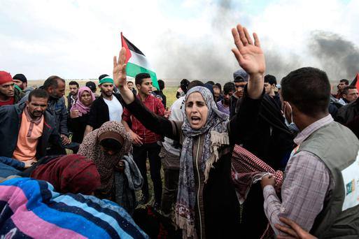 Bloody clashes: Palestinian protesters wave their national flag and gesture during a demonstration commemorating Land Day near the border with Israel, east of Khan Yunis, in the southern Gaza Strip. Photo: Said Khatib/Getty
