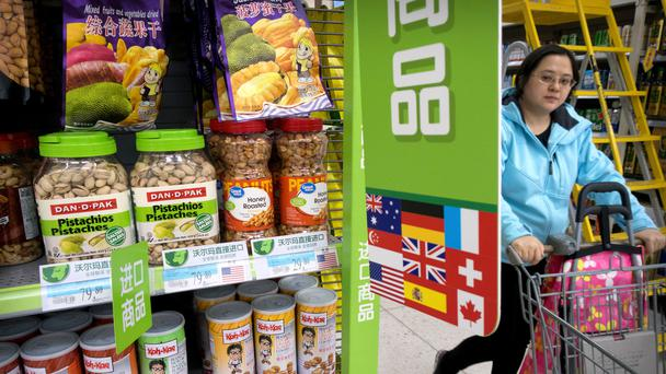 A woman pushes a shopping trolley past a display of nuts imported from the US at a supermarket in Beijing (Mark Schiefelbein/AP)