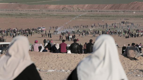Palestinian women sit on a hill as Israeli soldiers fire tear gas at protesters (Adel Hana/AP)