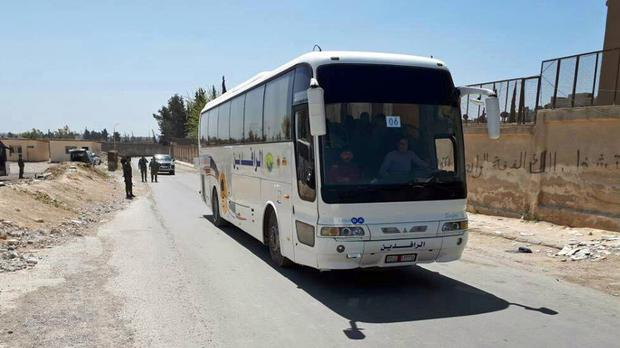Syrian government forces overseeing the evacuation by bus of Army of Islam fighters from the besieged town of Douma (SANA via AP)