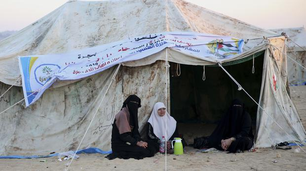Palestinian women sit outside their tent set up in front of the Gaza Strip border with Israel (Adel Hana/AP)