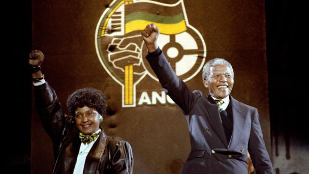 Nelson Mandela, with wife Winnie, gives the famous clench-fist salute of the African National Congress at Wembley Stadium (PA)