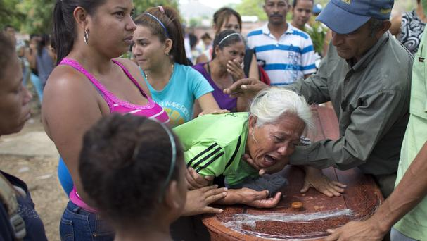 A woman grieves over the coffin containing the remains of Jose Manuel Perez, 28, at the Municipal Cemetery of Valencia, Venezuela (Ariana Cubillos/AP)