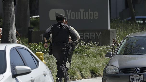 Officers run toward a YouTube office in San Bruno, California (Jeff Chiu/AP)