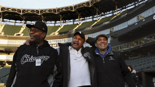 Chicago White Sox groundskeeper Nevest Coleman, centre, laughs with friend and fellow grounds crew members (Nancy Stone/AP)