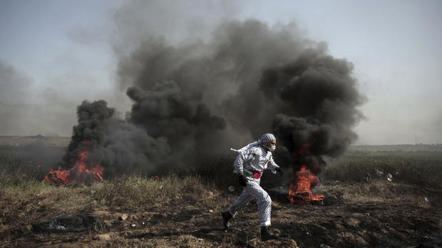 A Palestinian protester runs out of black smoke of burning tyres during a protest at the Gaza Strip (AP)