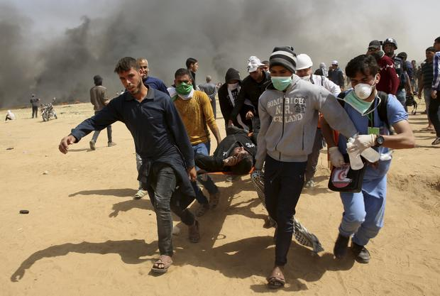 Protesters carry away a wounded youth (Adel Hana/AP)