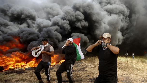 Palestinian protesters chant slogans next to burning tyres during clashes with Israeli troops (Adel Hana/AP)