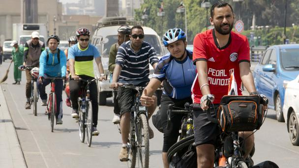 Mohammed Nufal is followed by supporters as he rides on Qasr El-Nile Bridge in Cairo (Amr Nabil/AP)