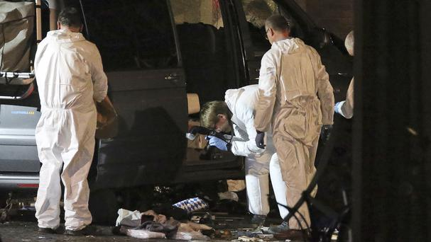 Forensic experts work on the scene (David Young/dpa/AP)