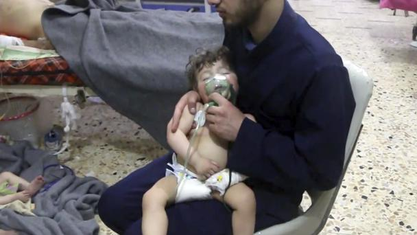 A medical worker giving toddlers oxygen (Syrian Civil Defence White Helmets via AP)