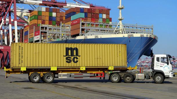 A lorry transports a shipping container at a port in Qingdao, in east China's Shandong province (Chinatopix via AP)