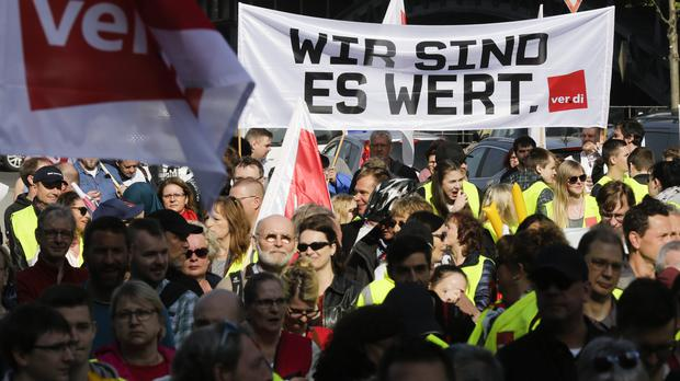 Members of the ver.di union attend a rally as part of a public sector pay strike in Berlin (Markus Schreiber/AP)