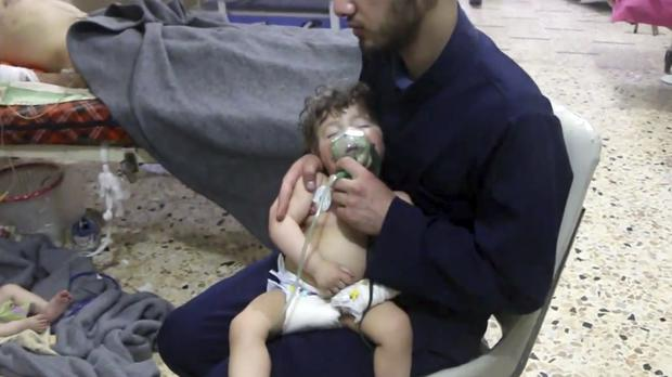 A medical worker giving a toddler oxygen following an alleged poison gas attack (Syrian Civil Defence White Helmets via AP)