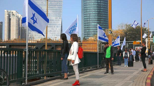 People stand still in memory of victims of the Holocaust in Tel Aviv (Ariel Schalit/AP)