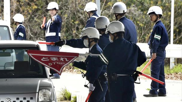 Police officers inspect cars at a checkpoint in the hunt for an escaped thief (Shingo Nishizume/Kyodo News via AP)