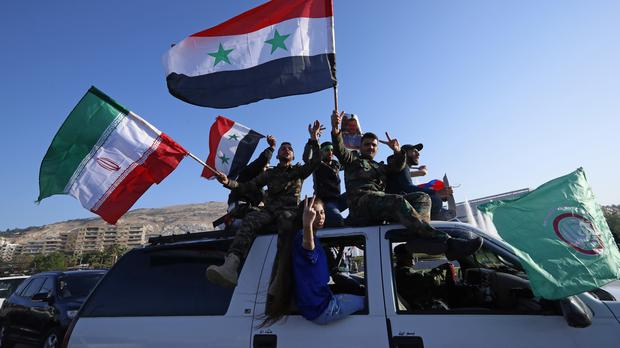 Syrian government supporters wave Syrian, Iranian and Russian flags (Hassan Ammar/AP)
