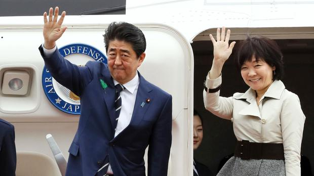 Japanese prime minister Shinzo Abe waves with his wife Akie Abe while boarding his plane before departure for the US (Kenzaburo Fukuhara/AP)
