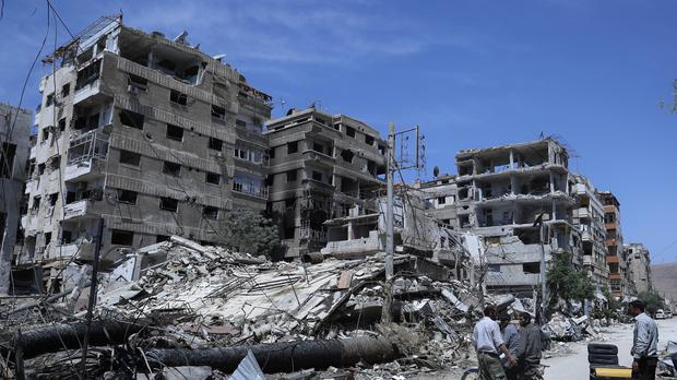 People stand in front of damaged buildings, in the town of Douma (Hassan Ammar/AP)
