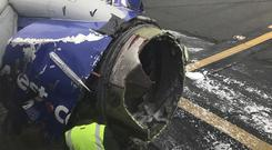 The engine on a Southwest Airlines plane is inspected as it sits on the runway at the Philadelphia International Airport after it made an emergency landing (Amanda Bourman via AP)