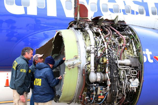 National Transportation Safety Board investigators examine damage to the engine of the Southwest Airlines plane. Photo: AP
