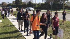 David Hogg, a student activist from Marjory Stoneman Douglas High School, speaks to a student as they walk out of their school
