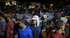 Migrants link arms to protect their families as riot police try to keep local protesters away