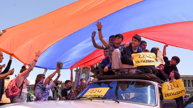 Protesters hold a huge Armenian national flag as they gather in Republic Square in Yerevan (Narek Aleksanyan/AP)