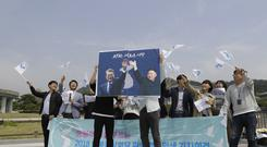 South Koreans hold a banner showing Moon Jae-in and Kim Jong Un to welcome the planned summit (Lee Jin-man/AP)