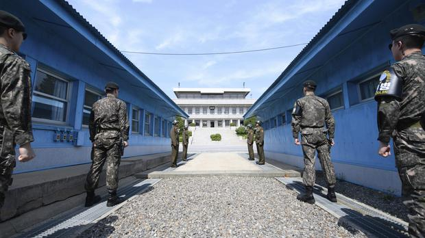 Four North Korean soldiers, centre far, and four South Korean soldiers, right and left, stand at the border village of Panmunjom (Hwang Kwang-mo/AP)