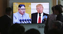 Kim Jong Un and Donald Trump pictured on a TV screen (Ahn Young-joon/AP)