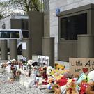 A car drives past flowers and other tributes for Alfie Evans outside Warsaw's UK embassy (Alik Keplicz/AP)