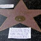 Bill Cosby's star on the Hollywood Walk Fame is tagged with a 'Guilty on All 3 Counts!' note (AP Photo/Damian Dovarganes)