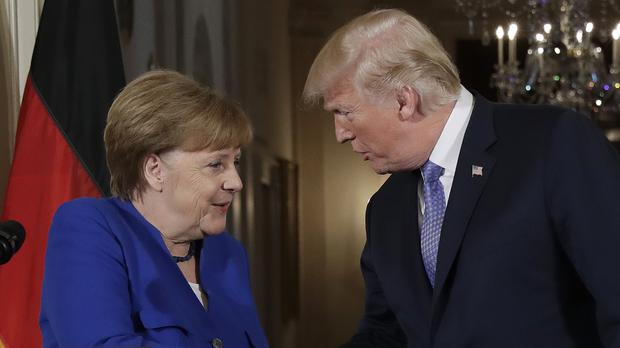 President Donald Trump shakes hands with German Chancellor Angela Merkel during a news conference in the East Room of the White House (Evan Vucci/AP)
