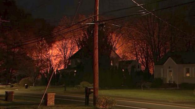 A fire behind a house in Connecticut. (WFSB-TV via AP)