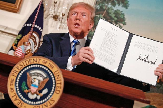 US President Donald Trump holds up a memorandum that re-instates sanctions on Iran after he announced his decision to withdraw the US from the 2015 Iran nuclear deal at the White House. Photo: Reuters