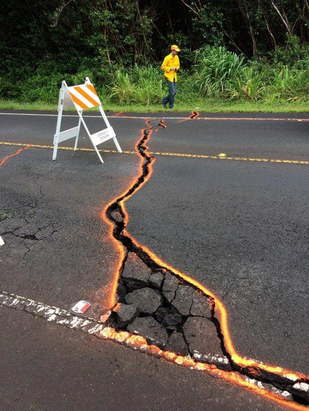 Scientists measure cracks in the road in Hawaii. Photo: Reuters