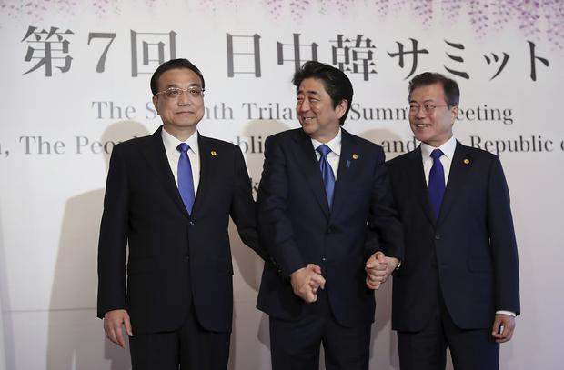 The summit hopes to improve the sometimes-frayed ties among the three north-east Asian neighbours. (Eugene Hoshiko/AP)
