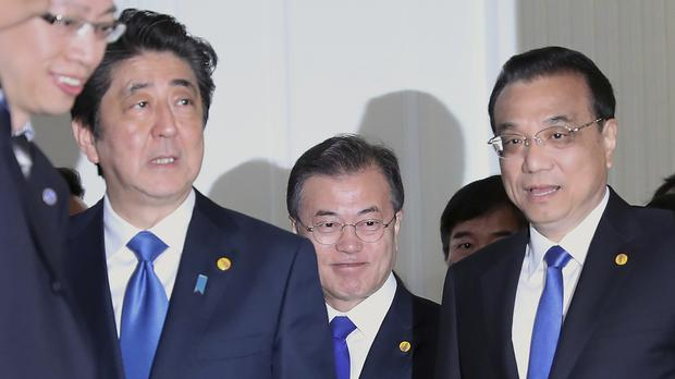 China's Li Keqiang, right, Japan's Shinzo Abe, left, and South Korean President Moon Jae-in at the summit in Tokyo (Eugene Hoshiko/AP)