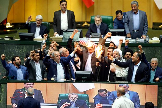"Iranian parliamentarians burn two pieces of paper representing the US flag and the nuclear deal and chant slogans against America, shouting: ""Death to America!"" Photo: AP"